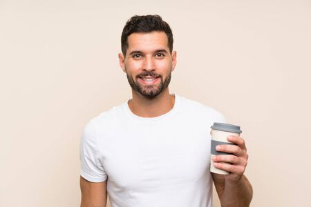 Young man with beard holding a take away coffee over isolated blue background smiling a lot Stock fotó