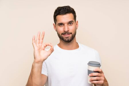 Young man with beard holding a take away coffee over isolated blue background showing ok sign with fingers Stock fotó