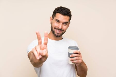 Young man with beard holding a take away coffee over isolated blue background smiling and showing victory sign Stok Fotoğraf - 132036334
