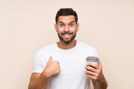 Young man with beard holding a take away coffee over isolated blue background with surprise facial expression
