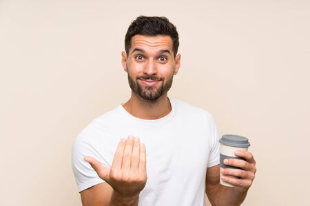Young man with beard holding a take away coffee over isolated blue background inviting to come with hand. Happy that you came Stock fotó