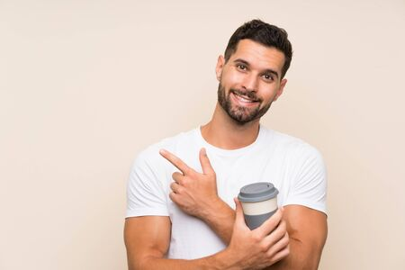 Young man with beard holding a take away coffee over isolated blue background pointing to the side to present a product Stock fotó