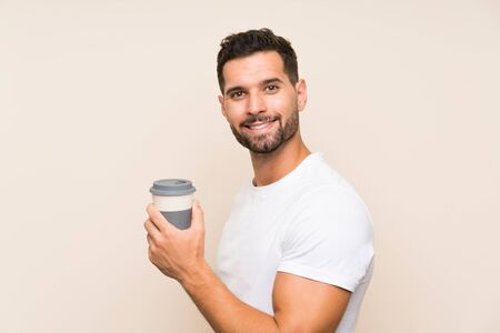 Handsome man over isolated background holding a take away coffee