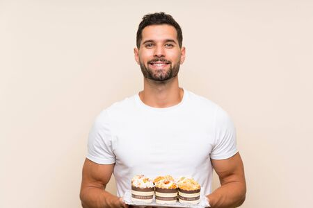 Handsome man holding muffin cake over isolated background smiling a lot