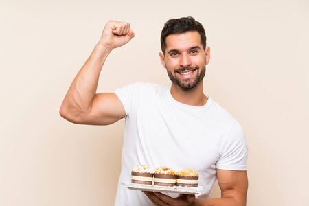 Handsome man holding muffin cake over isolated background celebrating a victory Stok Fotoğraf - 132036267