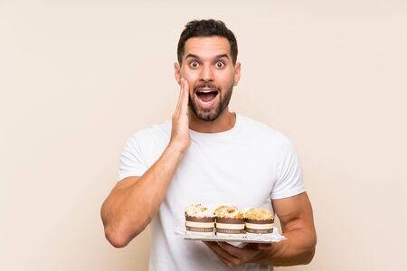 Hombre guapo sosteniendo pastel de muffin sobre fondo aislado con sorpresa y expresión facial conmocionada
