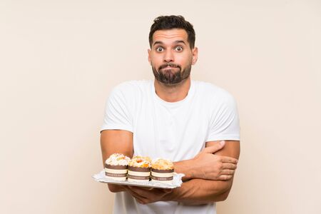 Handsome man holding muffin cake over isolated background making doubts gesture while lifting the shoulders