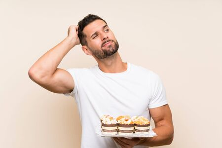 Handsome man holding muffin cake over isolated background having doubts and with confuse face expression Фото со стока