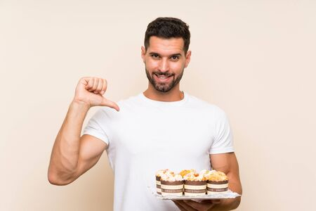 Handsome man holding muffin cake over isolated background proud and self-satisfied Stock fotó
