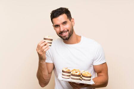 Handsome man holding muffin cake over isolated background Stock fotó