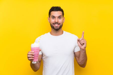 Young man with strawberry milkshake over isolated yellow background pointing up a great idea