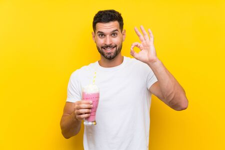 Young man with strawberry milkshake over isolated yellow background showing ok sign with fingers