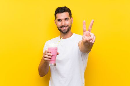 Young man with strawberry milkshake over isolated yellow background smiling and showing victory sign