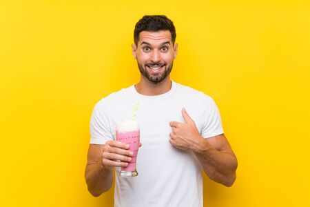 Young man with strawberry milkshake over isolated yellow background with surprise facial expression