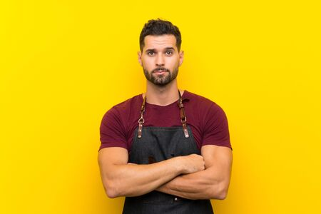 Barber man in an apron keeping arms crossed