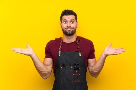 Barber man in an apron having doubts with confuse face expression