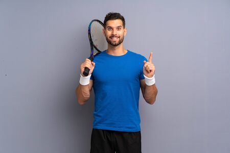 Handsome young tennis player man pointing up a great idea Imagens
