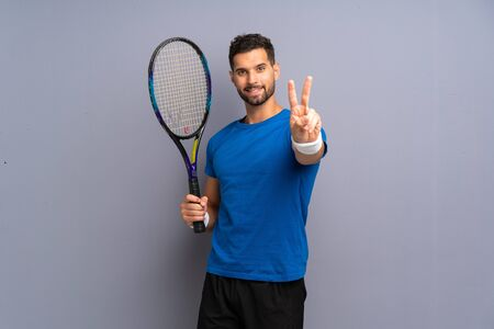 Handsome young tennis player man smiling and showing victory sign Stok Fotoğraf - 132035268