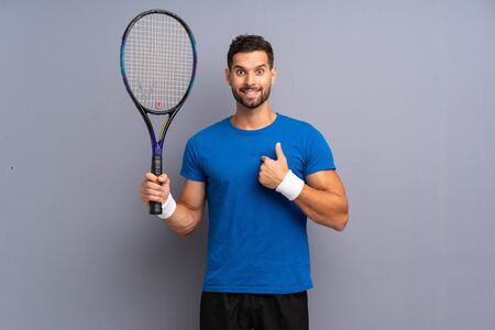 Handsome young tennis player man with surprise facial expression Stok Fotoğraf