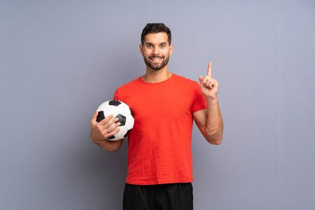 Handsome young football player man over isolated white wall pointing up a great idea Imagens