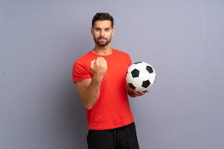 Handsome young football player man over isolated white wall inviting to come with hand. Happy that you came Banco de Imagens