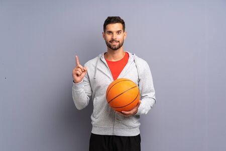 Handsome young basketball player man pointing up a great idea