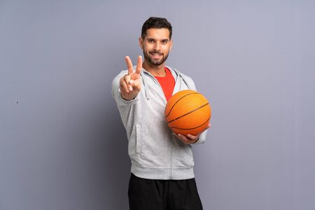 Handsome young basketball player man smiling and showing victory sign