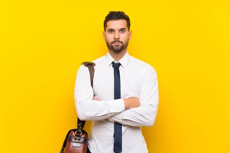 Handsome businessman over isolated yellow background thinking an idea