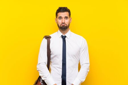 Handsome businessman over isolated yellow background sad