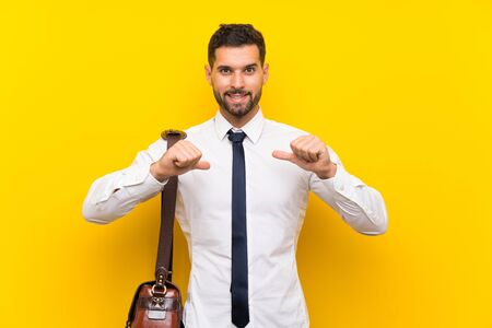 Handsome businessman over isolated yellow background proud and self-satisfied Zdjęcie Seryjne