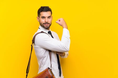 Handsome businessman over isolated yellow background making strong gesture