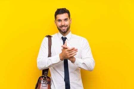 Handsome businessman over isolated yellow background applauding