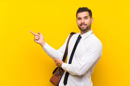 Handsome businessman over isolated yellow background pointing finger to the side