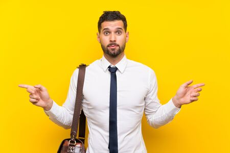 Handsome businessman over isolated yellow background pointing to the laterals having doubts