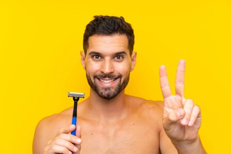 Man shaving his beard smiling and showing victory sign Stok Fotoğraf - 132034998