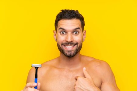 Man shaving his beard with surprise facial expression