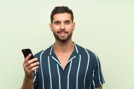 Young handsome man with a mobile smiling a lot Фото со стока