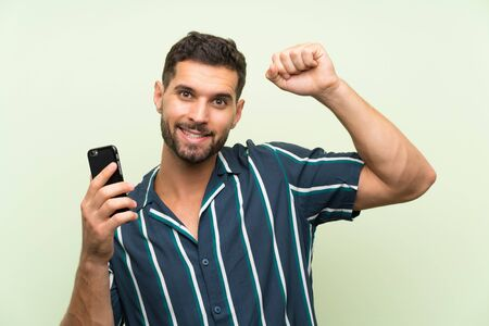 Young handsome man with a mobile celebrating a victory