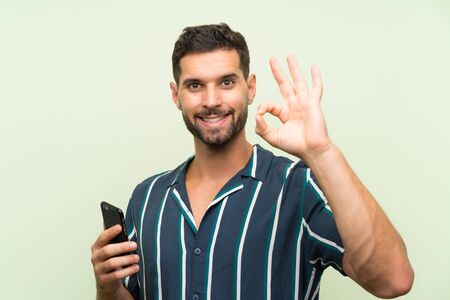 Young handsome man with a mobile showing ok sign with fingers