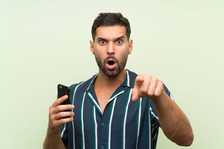 Young handsome man with a mobile surprised and pointing front Фото со стока