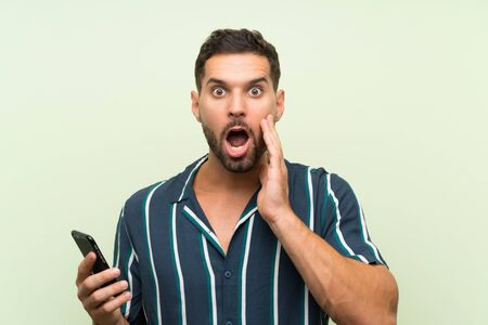 Young handsome man with a mobile with surprise and shocked facial expression
