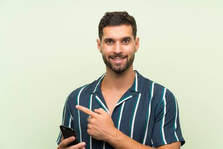 Young handsome man with a mobile pointing to the side to present a product