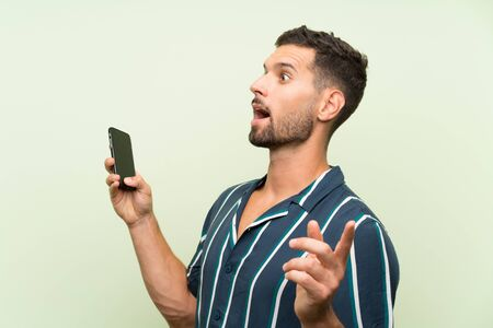 Young handsome man with a mobile with surprise facial expression Фото со стока - 132034939