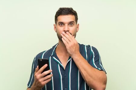 Young handsome man with a mobile with surprise facial expression