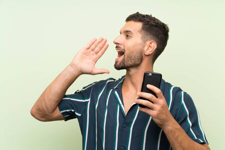 Young handsome man with a mobile shouting with mouth wide open Фото со стока