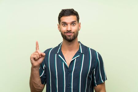 Handsome man over isolated background pointing with the index finger a great idea