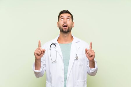 Young doctor man over isolated green wall pointing with the index finger a great idea