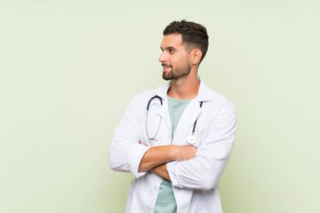 Young doctor man over isolated green wall looking to the side