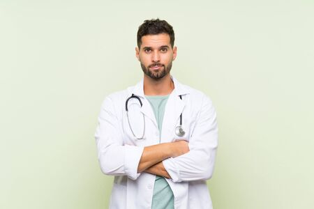 Young doctor man over isolated green wall keeping arms crossed Stock fotó