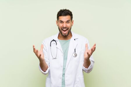 Young doctor man over isolated green wall unhappy and frustrated with something